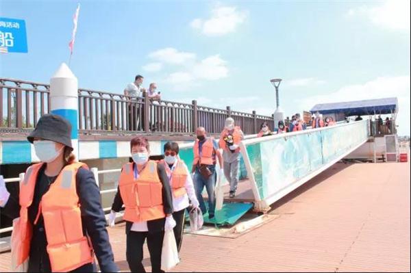 工作人员手持船牌号及应急药品引导家属有序登船